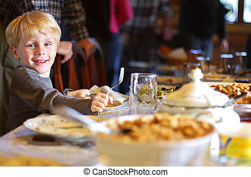 Child Sitting at Table for Holiday Dinner - a happy young...
