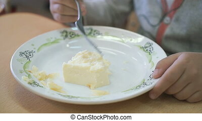 Child sitting at the table eating a scrambled