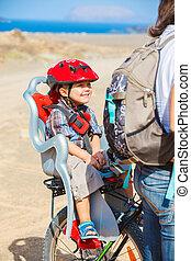child sitting by bicycle in crash helmet