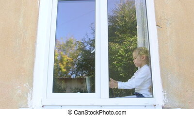Child sitting by the window and playing with digital tablet