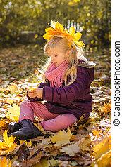 child sitting in autumn park