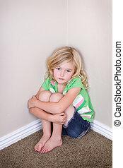 child sitting in corner