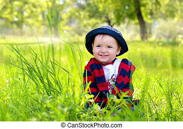 child sitting in grass and smiling