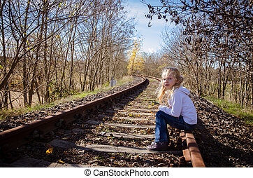 child sitting in railway