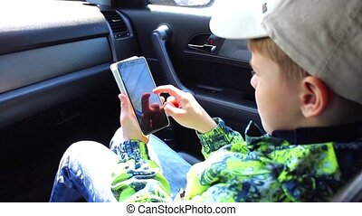 child sitting in the cars and playing with smartphone with smile on his face.