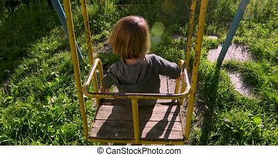 Child sitting in yard on old swing - Back view of child...