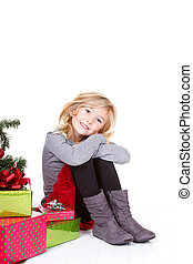 Child sitting next to a Christmas tree
