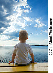Child sitting on a bench looking at the sea