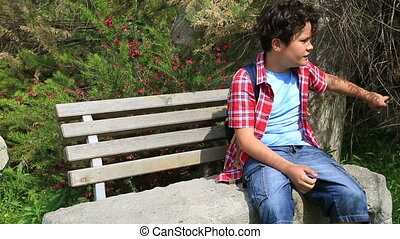 Child sitting on a park bench