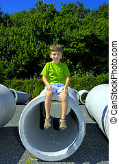 Child Sitting on a Pipe