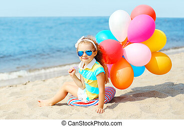 Child sitting on beach with colorful balloons near sea summer day
