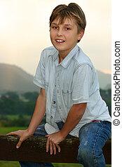 Child sitting on fence
