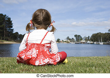 Child Sitting on Grass Looking at Boats on Lake