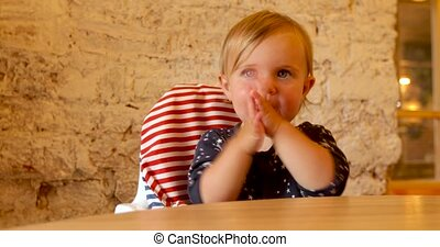 Child sitting on highchair clapping with hands - Playful...