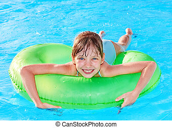 Child sitting on inflatable ring. - Children sitting on...