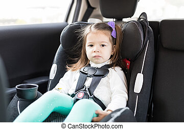 Child Sitting On Safety Seat In Car