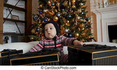 child sitting on sofa with gift boxes