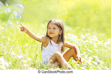 Child sitting on the grass in summer field, sunny day