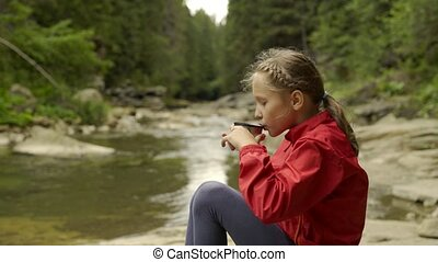 Child sitting on the mountain river bank - Sliding video of...