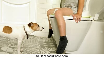 Child sitting on toilet in child seat with curios dog - Side...