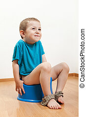 Child sitting on toilet potty - Little smiling child boy...