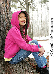 Child sitting under tree in winter