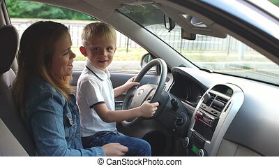 Child sitting with his mother's at the wheel of the car, they listen to music.