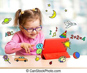 Child sitting with tablet computer and learning or playing ...