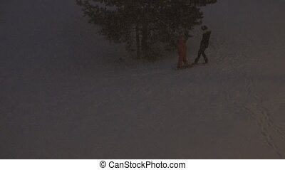 child skates with snowboard from small hill and fall snow. ...