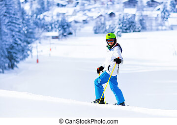 Child skiing in mountains.