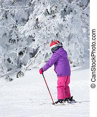 Child skiing on mountain peak