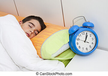 child sleeping in bed with alarm clock