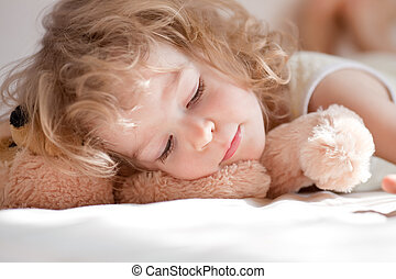 Child sleeping in bed with teddy