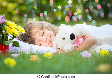 Happy child sleeping with toy teddy bear on green grass outdoors in spring garden