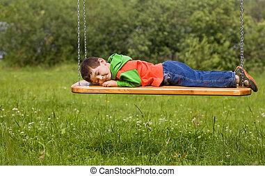 Child sleeping on a swing