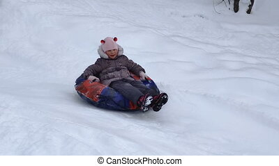 child slides on snow tubing