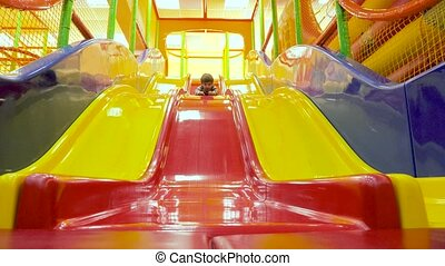 Child sliding down colorful slide play house in backyard....