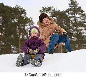 child sliding in the snow with her mother