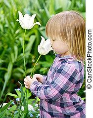 Child smelling flower