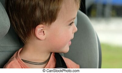 Kid looking at camera. Portrait of cute boy sitting in car seat. Child transportation safety. A cheerful baby waving his hand while sitting in a children's car seat