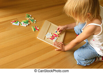 Child solving puzzle - 2-3 years old girl kneeling on the...