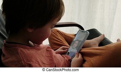 Cute boy talking with father video call using smartphone a sitting at armchair