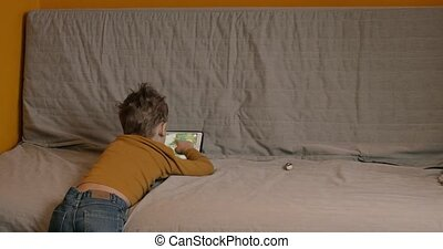 Child spending leisure with touch pad at home - MOSCOW,...
