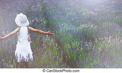 Child spinning in the field. Girl looking at the camera and waving hand. Girl is in the white hat. Butterfly is flying