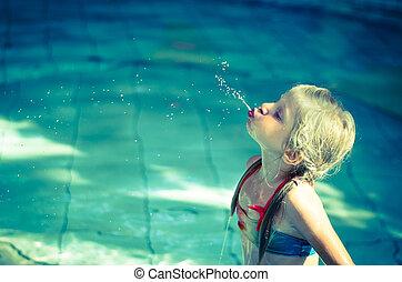 child spitting water