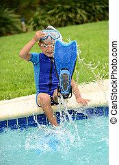 child splashing feet in pool