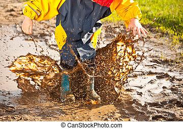 Child splashing in muddy puddle