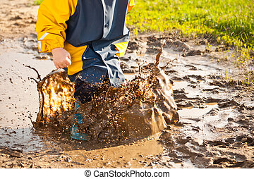 Child splashing in puddle