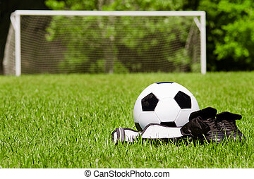 Child sports concept with soccer ball, cleats, shin guards ...