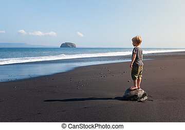 Child stand on big stone on black sand sea beach